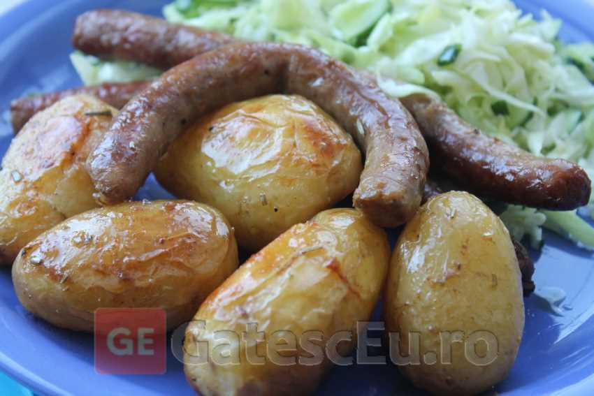 Cartofi noi cu carnaciori la cuptor
